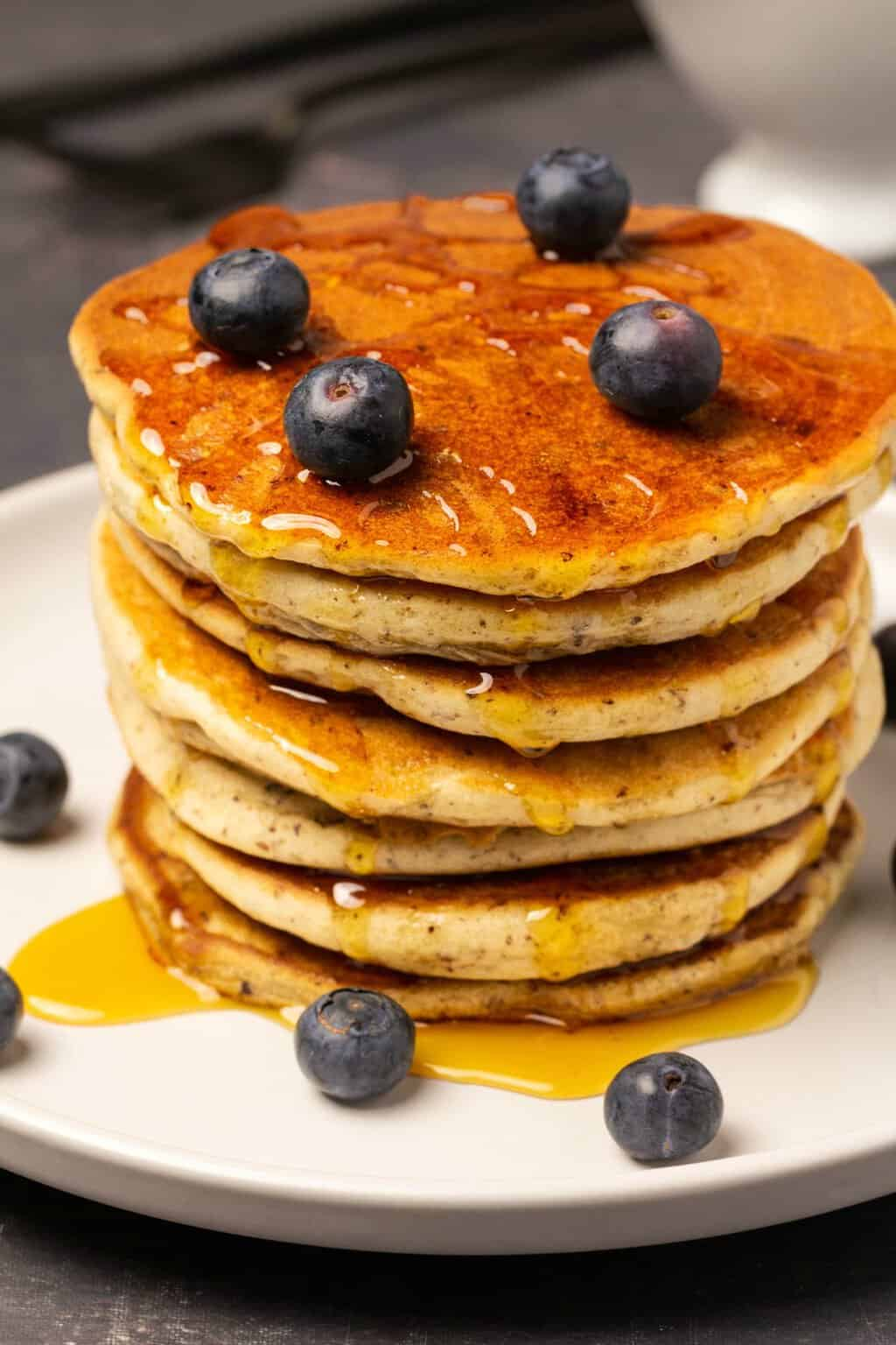 Vegan gluten free pancakes in a stack topped with syrup and fresh blueberries.