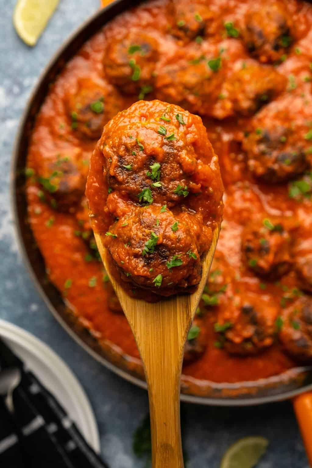 Vegan meatballs on a wooden spoon.