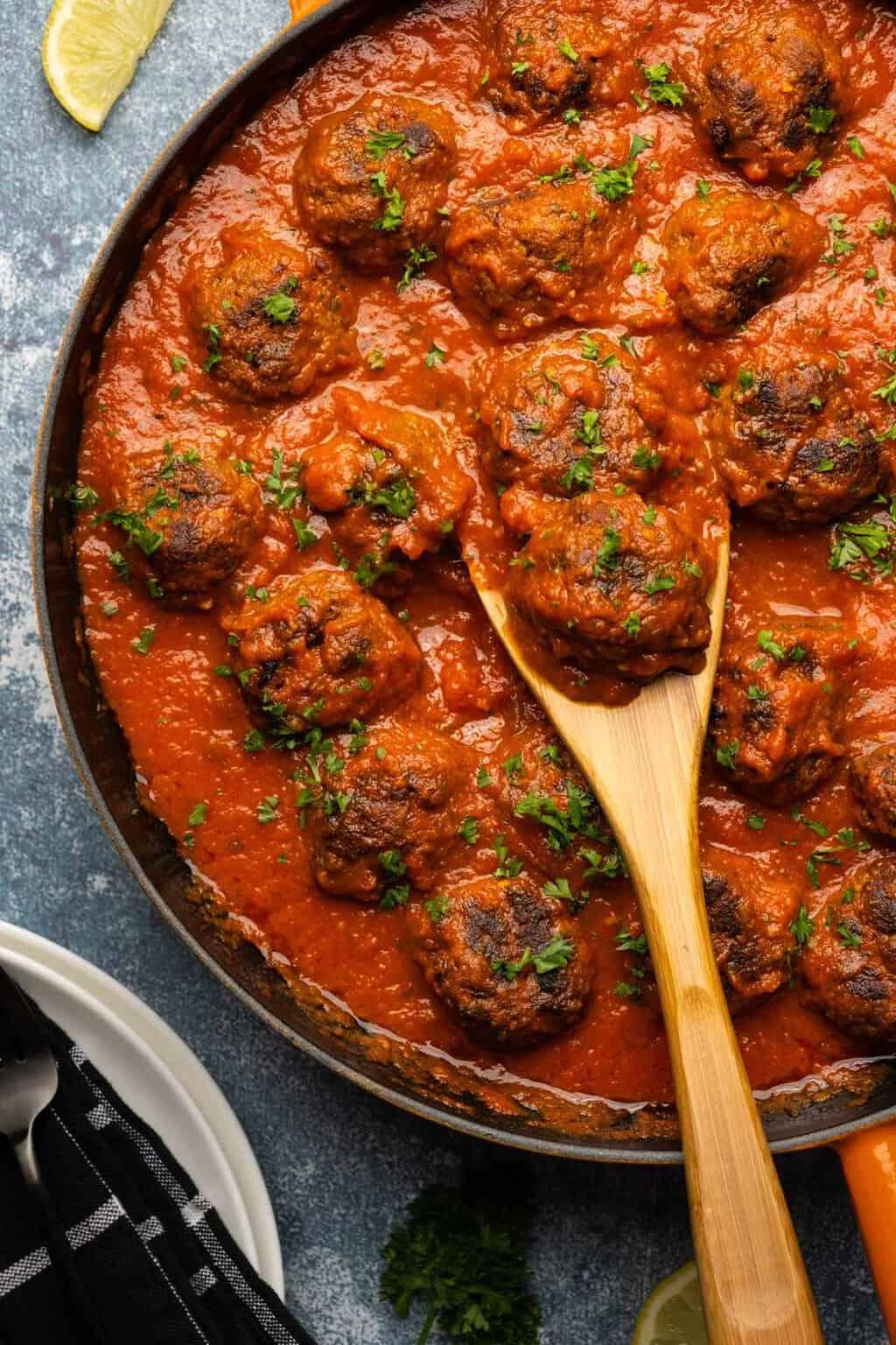 Vegan meatballs in a frying pan with marinara sauce.
