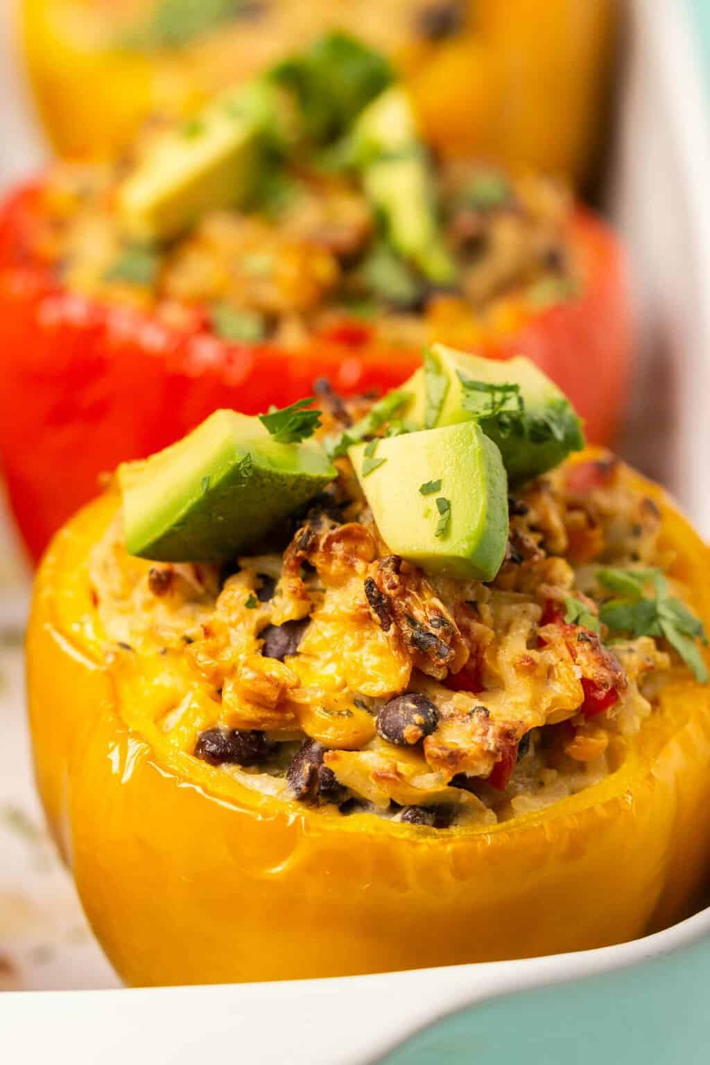 Vegan stuffed peppers topped with chopped avocado and cilantro.