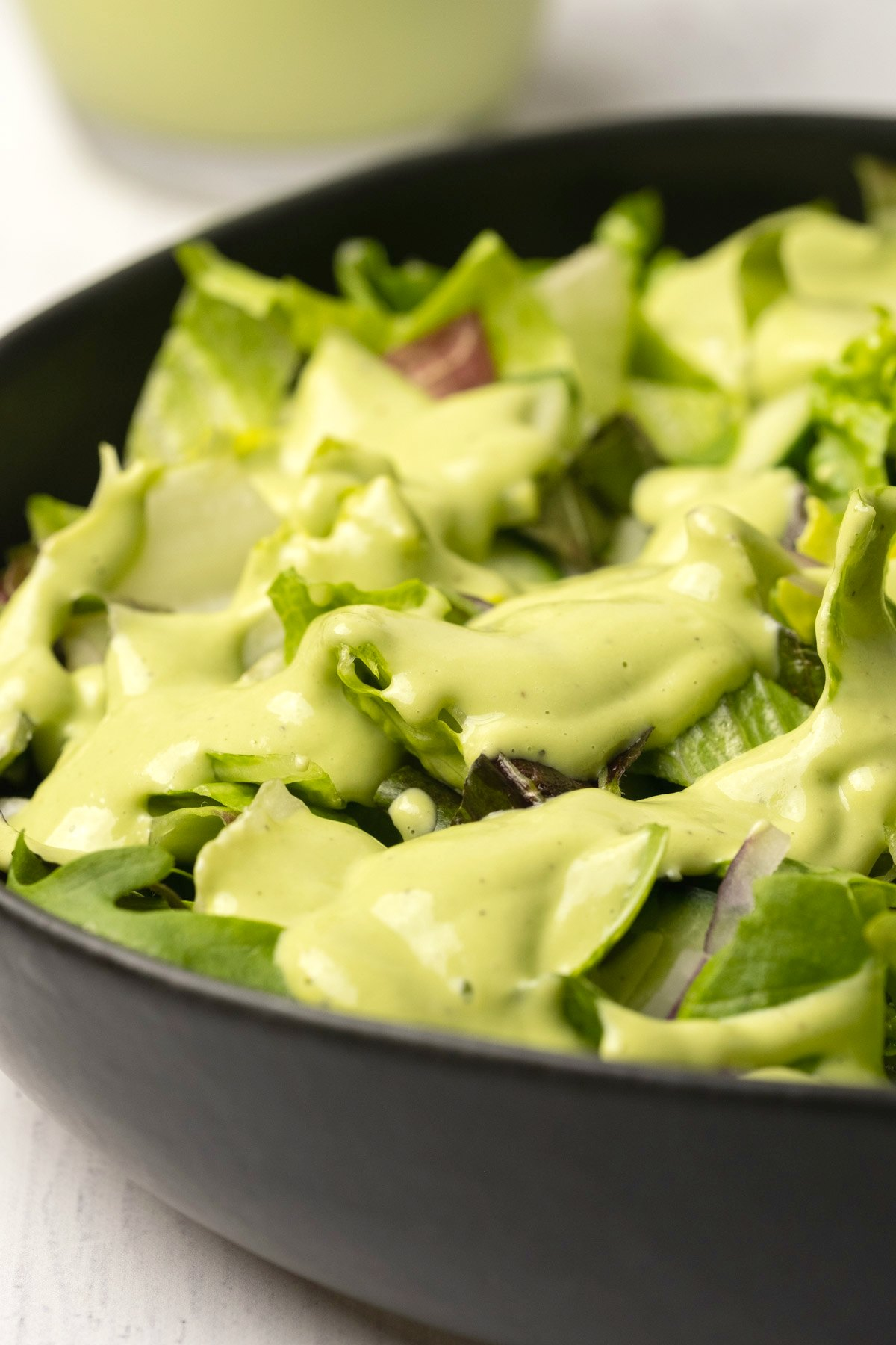 Green salad in a black bowl topped with cashew dressing.