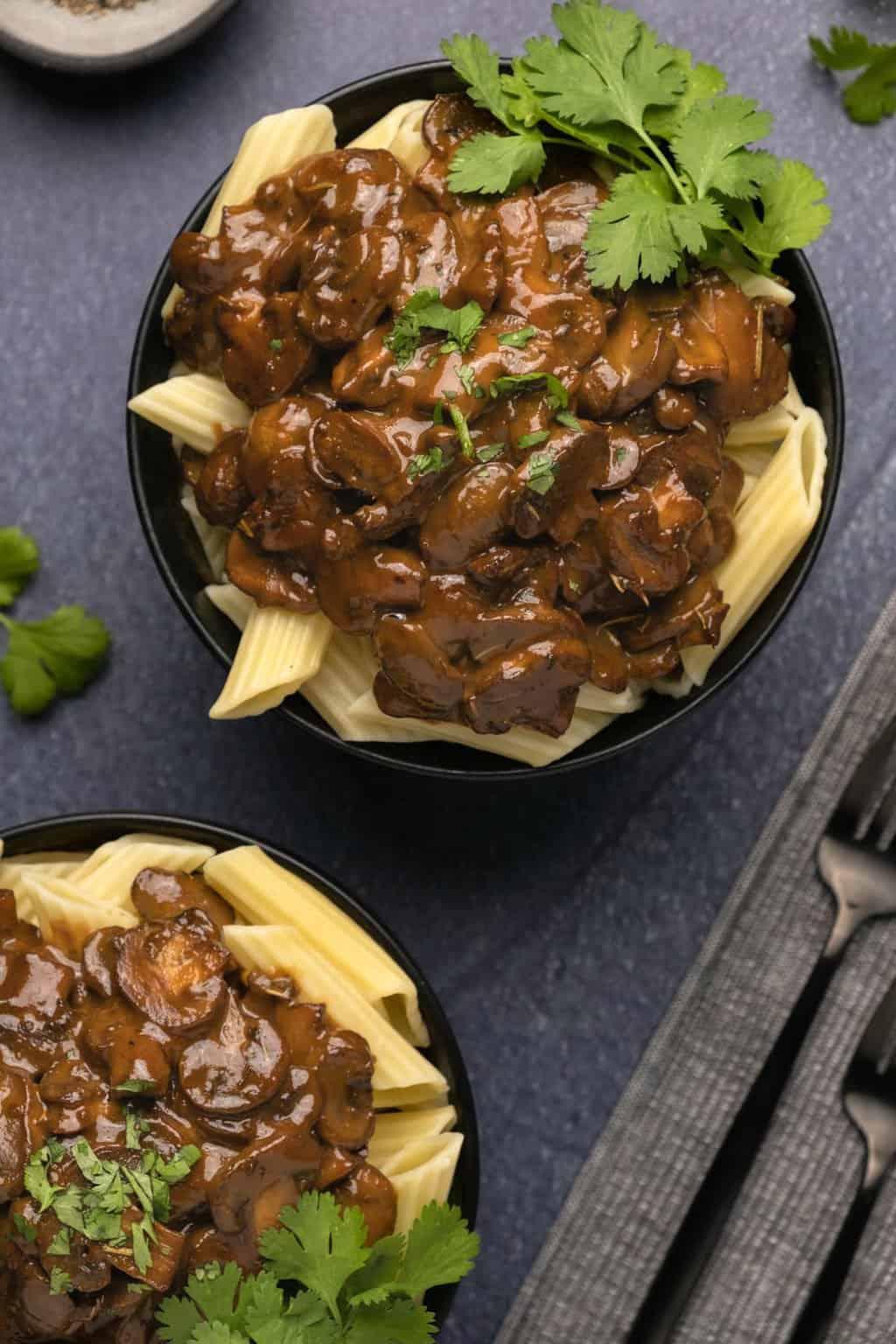 Dairy free mushroom sauce over penne in black bowls.