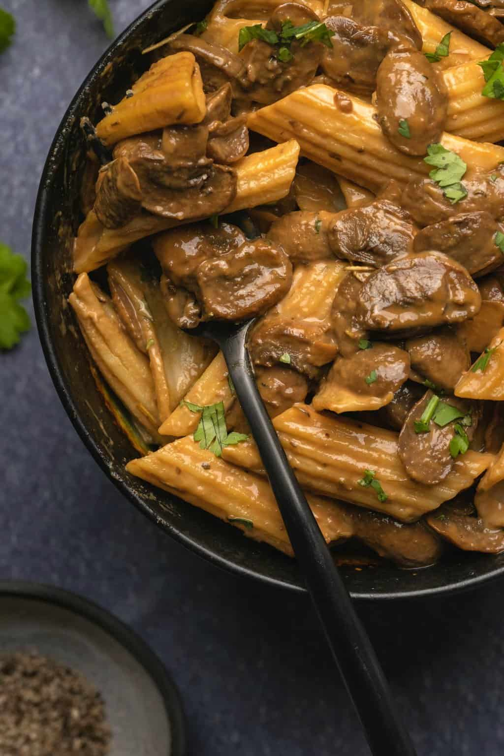 Penne with dairy free mushroom sauce and chopped cilantro in a black bowl.