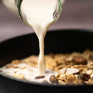 Almond milk pouring from a glass milk bottle onto a bowl of cereal.