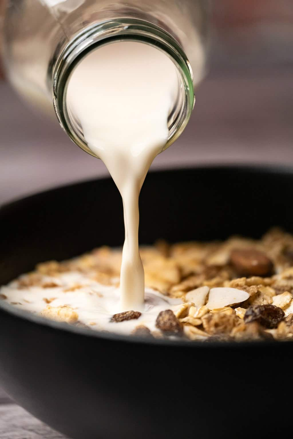 Almond milk pouring over cereal in a black bowl.