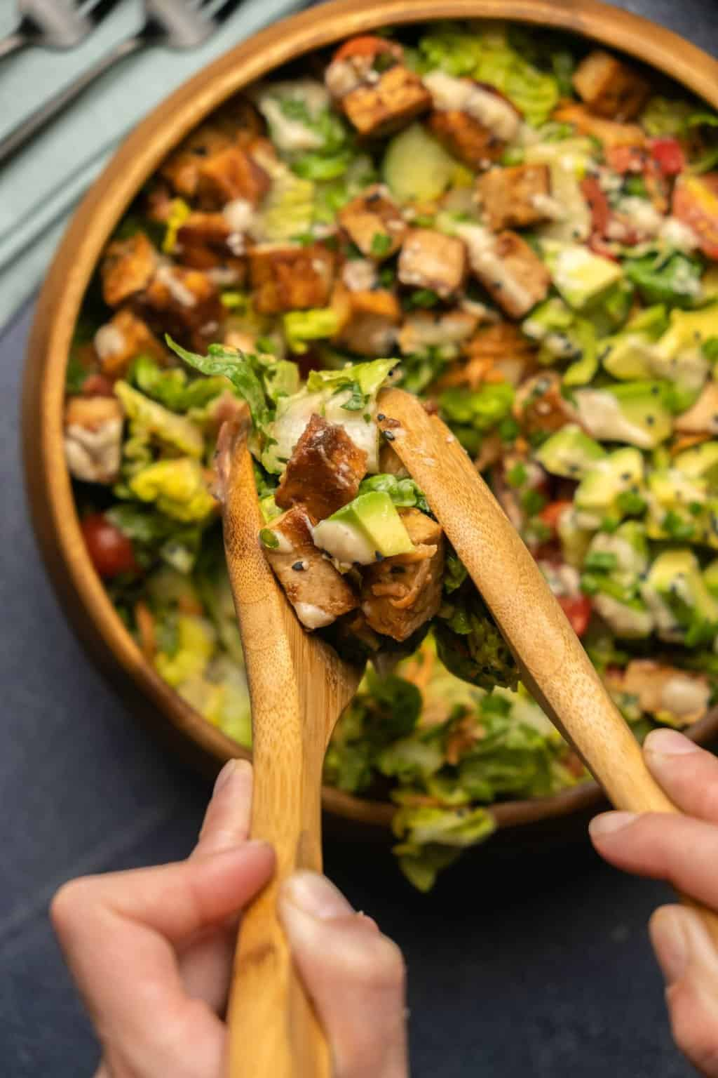 Dishing up tofu salad from a wooden bowl with wooden salad spoons.