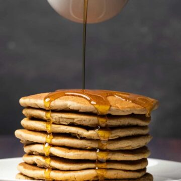 Syrup pouring from a glass jug over a stack of vegan protein pancakes on a white plate.