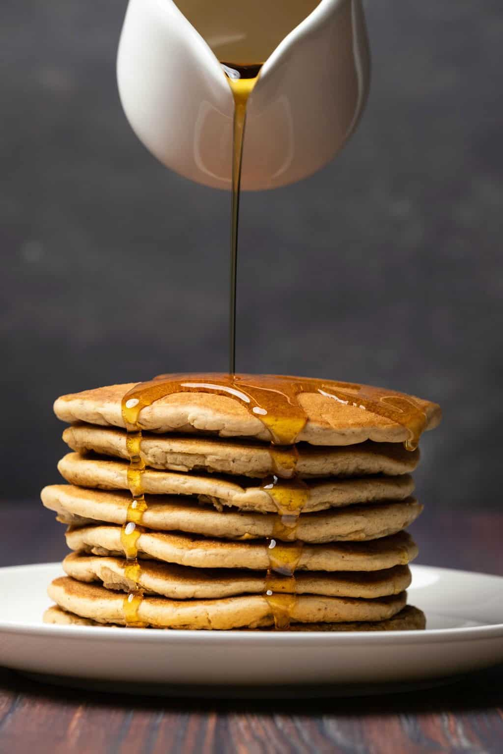 A stack of vegan protein pancakes with syrup pouring over the top.