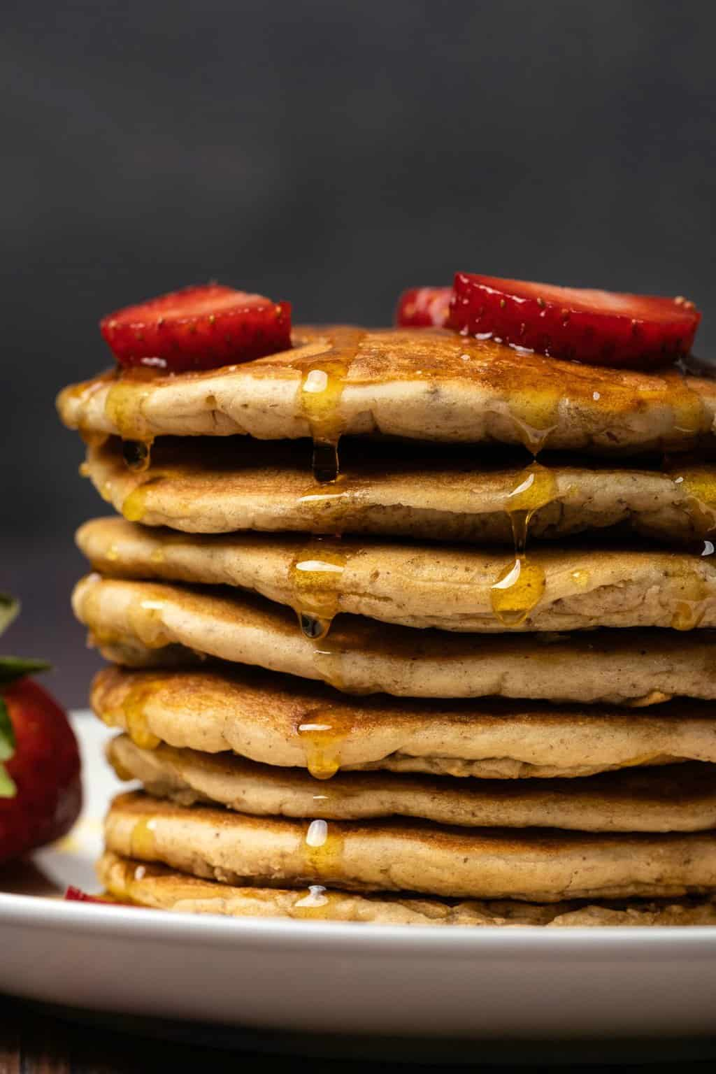 Vegan protein pancakes drizzled with syrup and topped with strawberries.