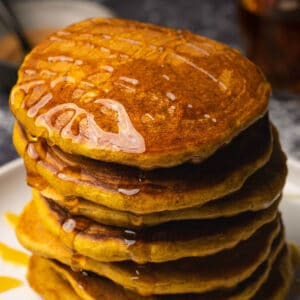 Stack of vegan pumpkin pancakes drizzled with syrup on a white plate.