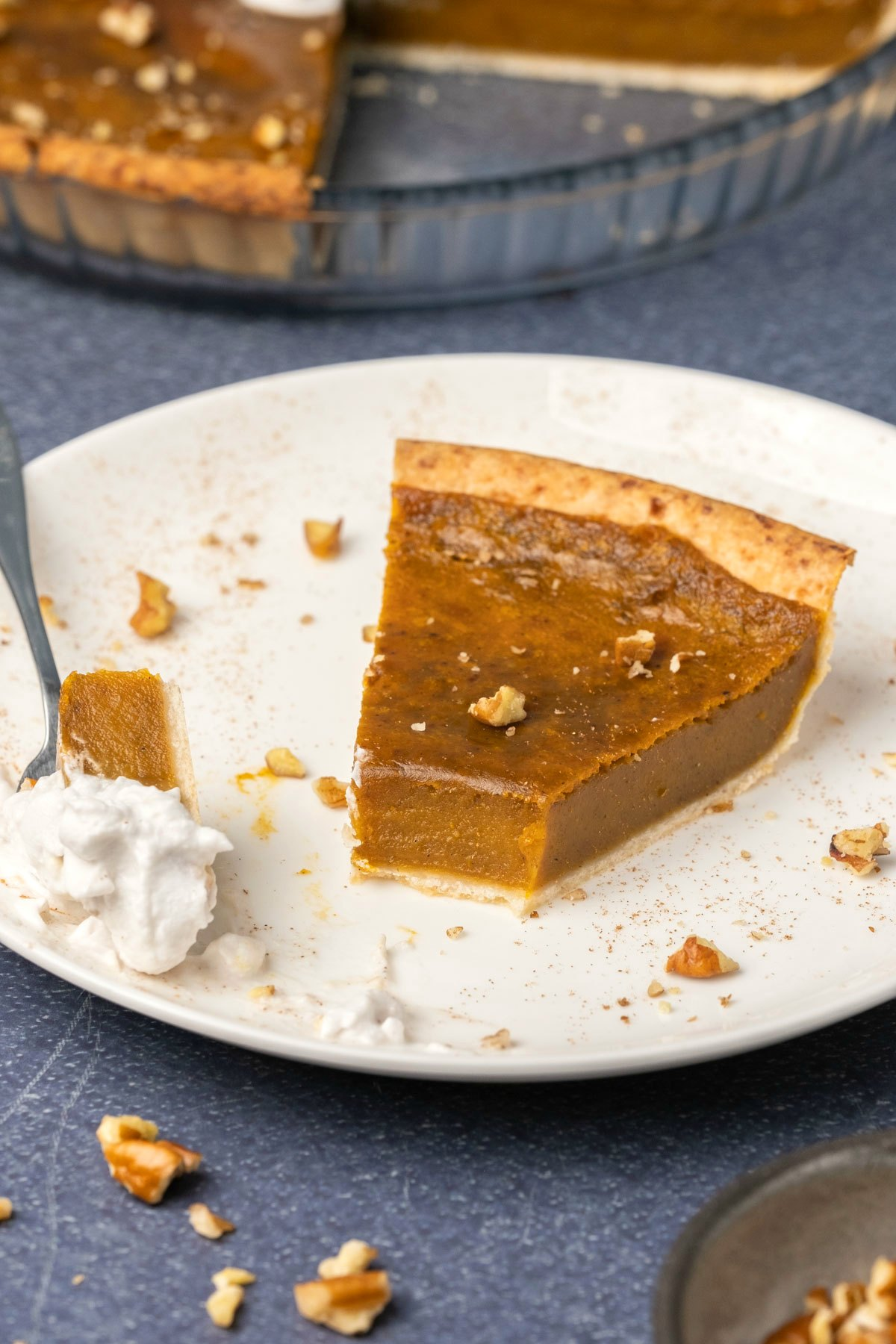 A slice of vegan sweet potato pie on a white plate with a cake fork.