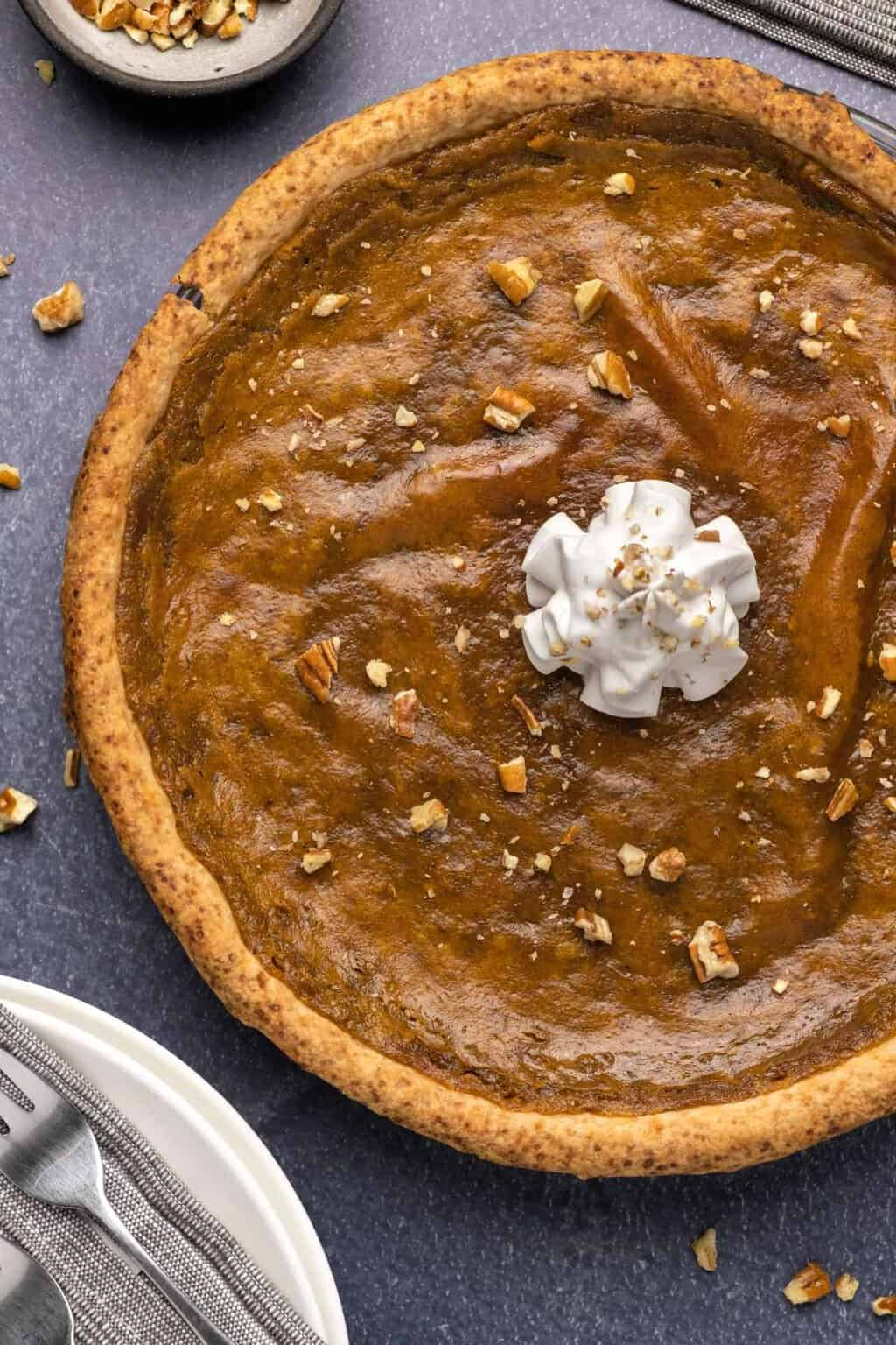 Vegan sweet potato pie topped with chopped pecans and vegan whipped cream.