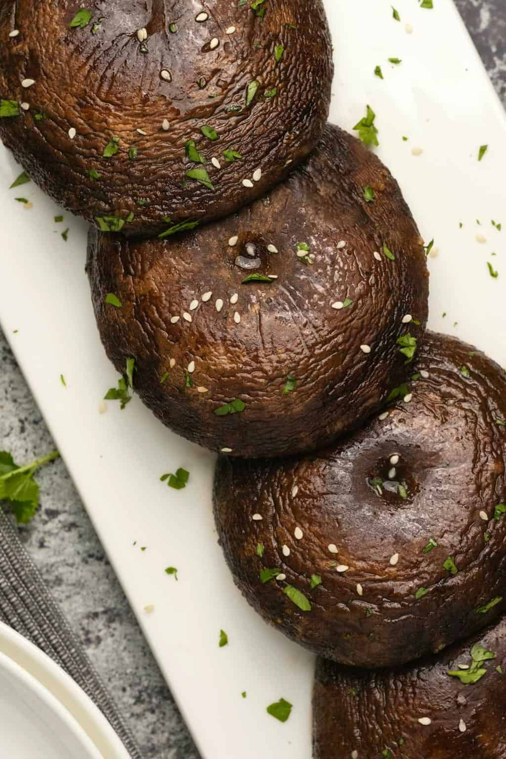 Baked portobello mushrooms sprinkled with chopped cilantro and sesame seeds on a white plate.