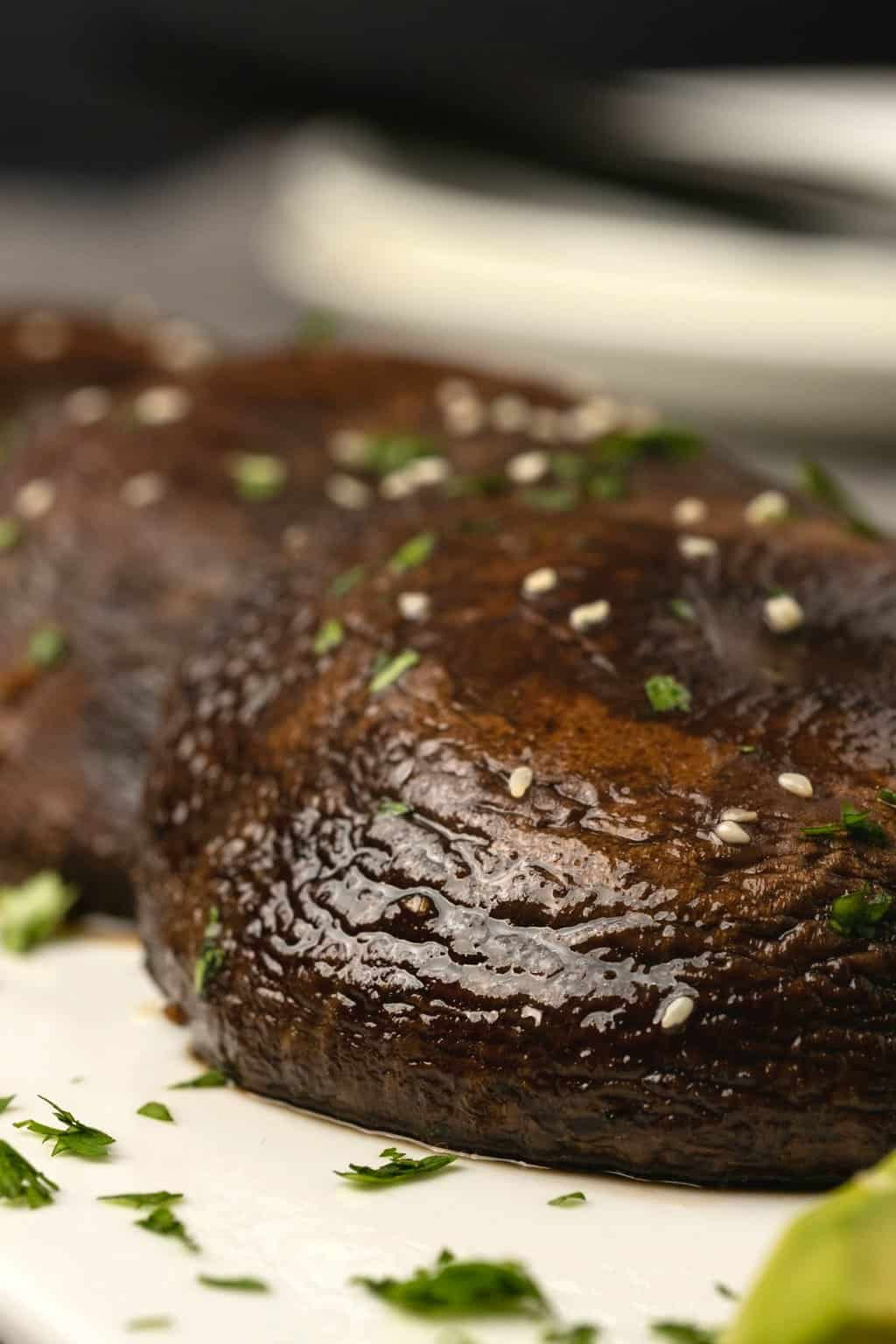 Baked portobello mushrooms on a white plate with sprinkled cilantro and sesame seeds.