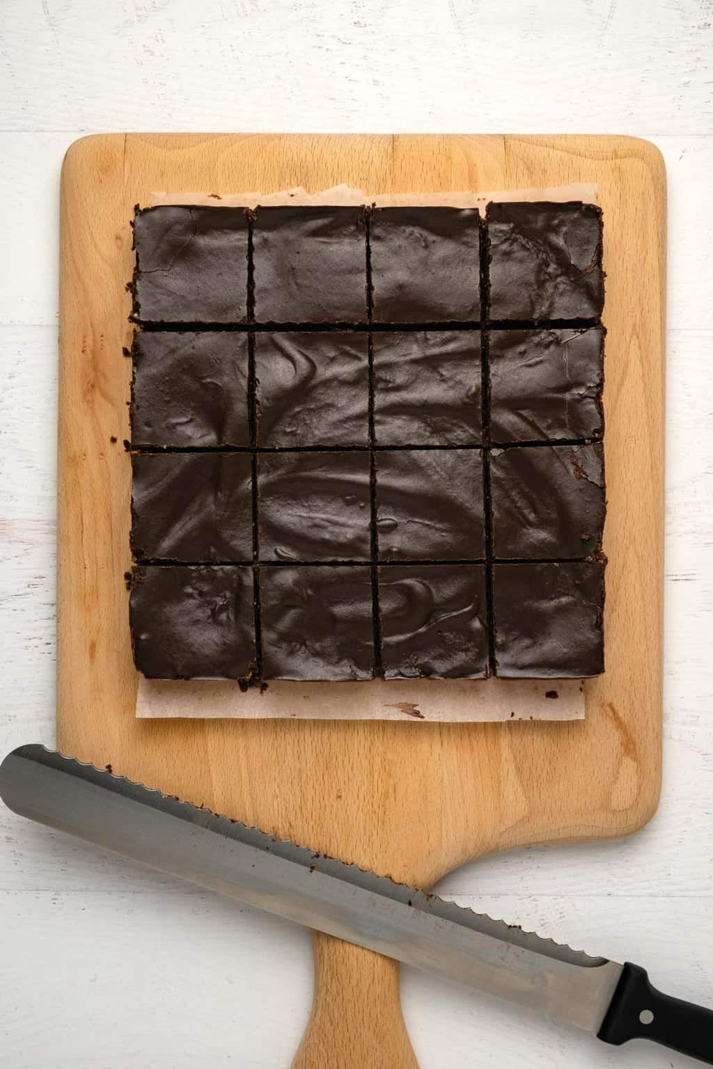 Raw vegan brownies cut into squares on a wooden board.