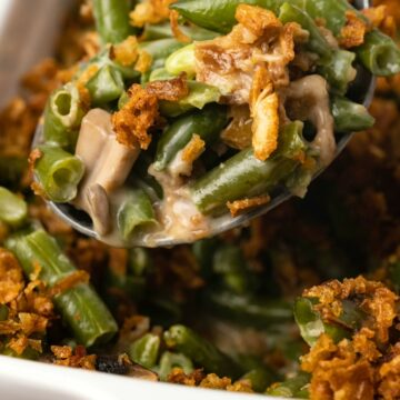 Vegan green bean casserole in a white dish with a serving spoon.