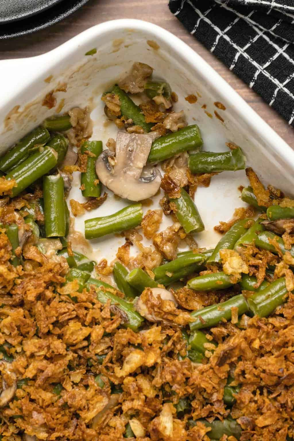 Vegan green bean casserole in a white dish with a portion removed.