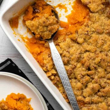 Vegan sweet potato casserole in a white dish with a serving spoon.