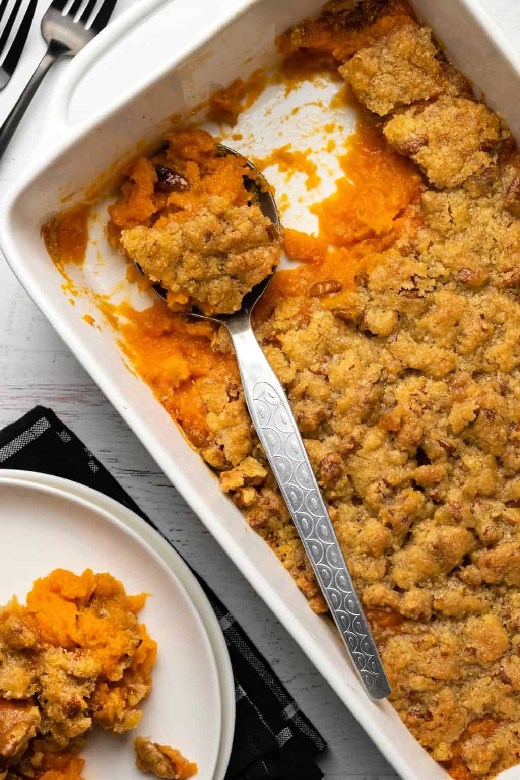 Vegan sweet potato casserole in a white dish with a silver serving spoon.