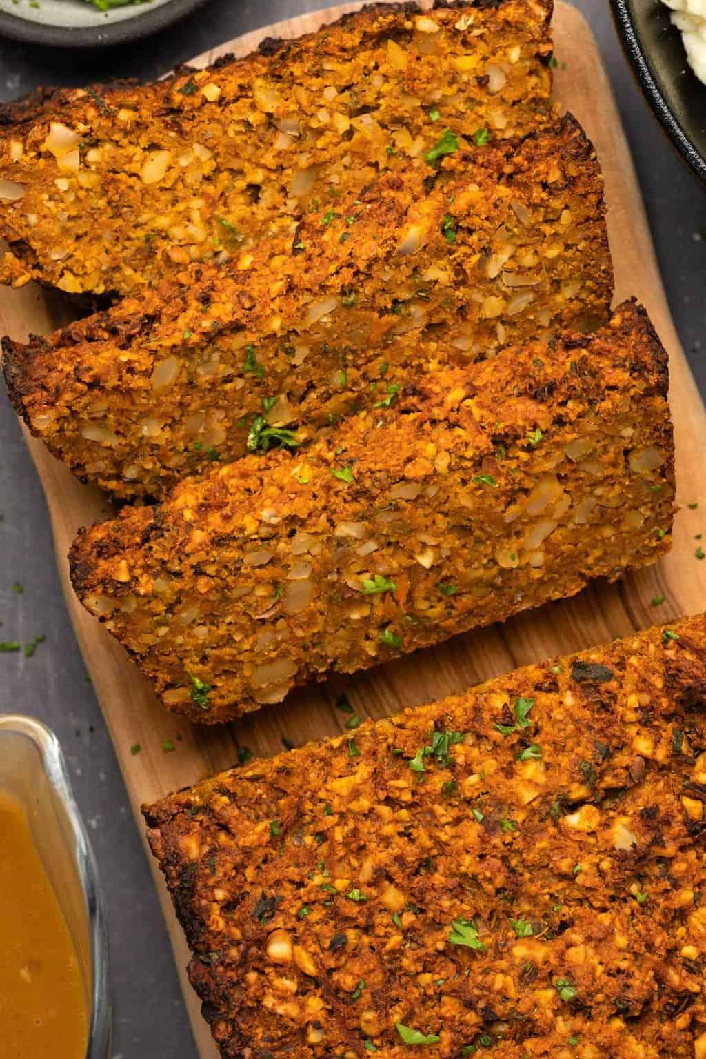 Slices of vegan nut roast on a wooden board.