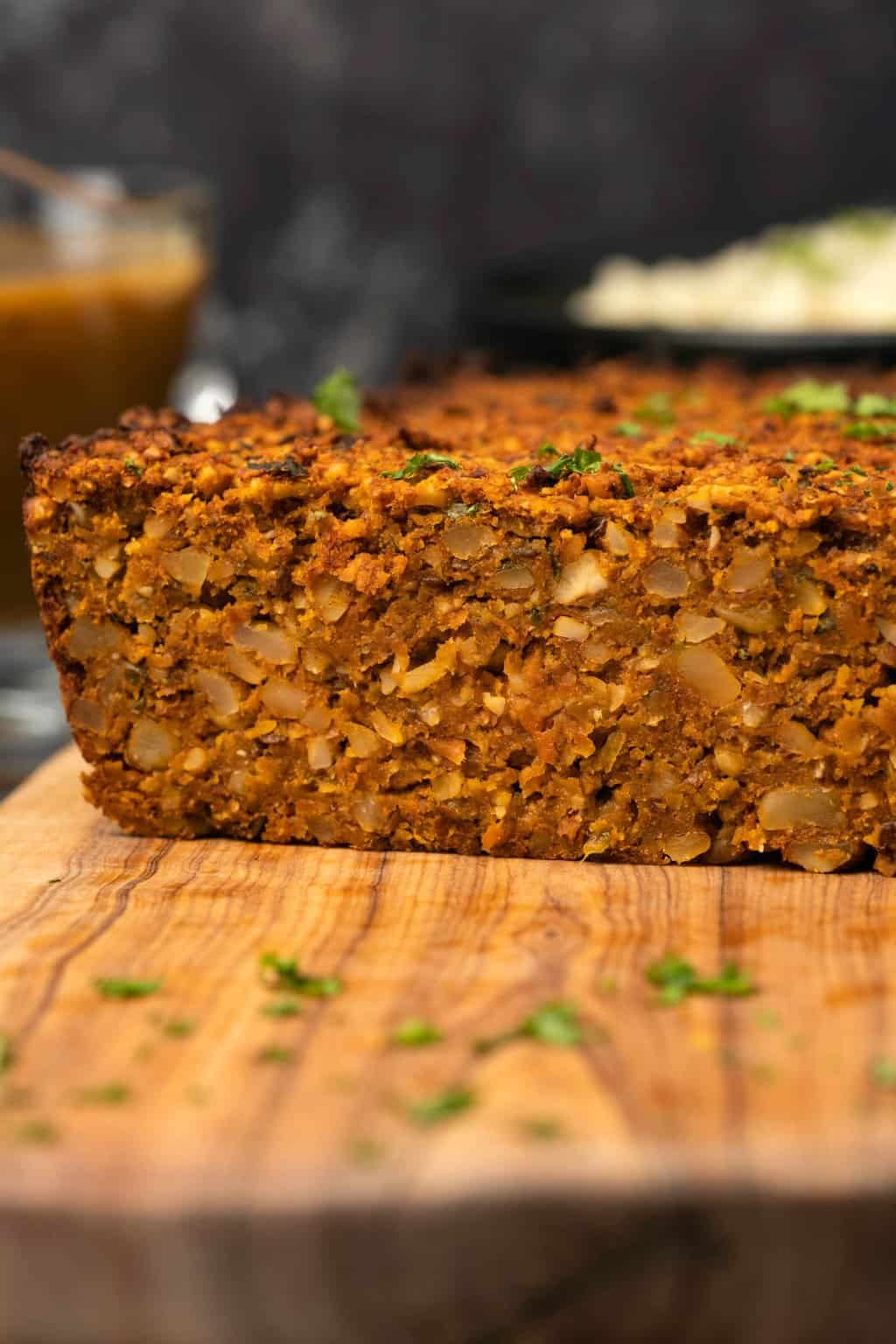 Nut roast with chopped parsley on a wooden board.