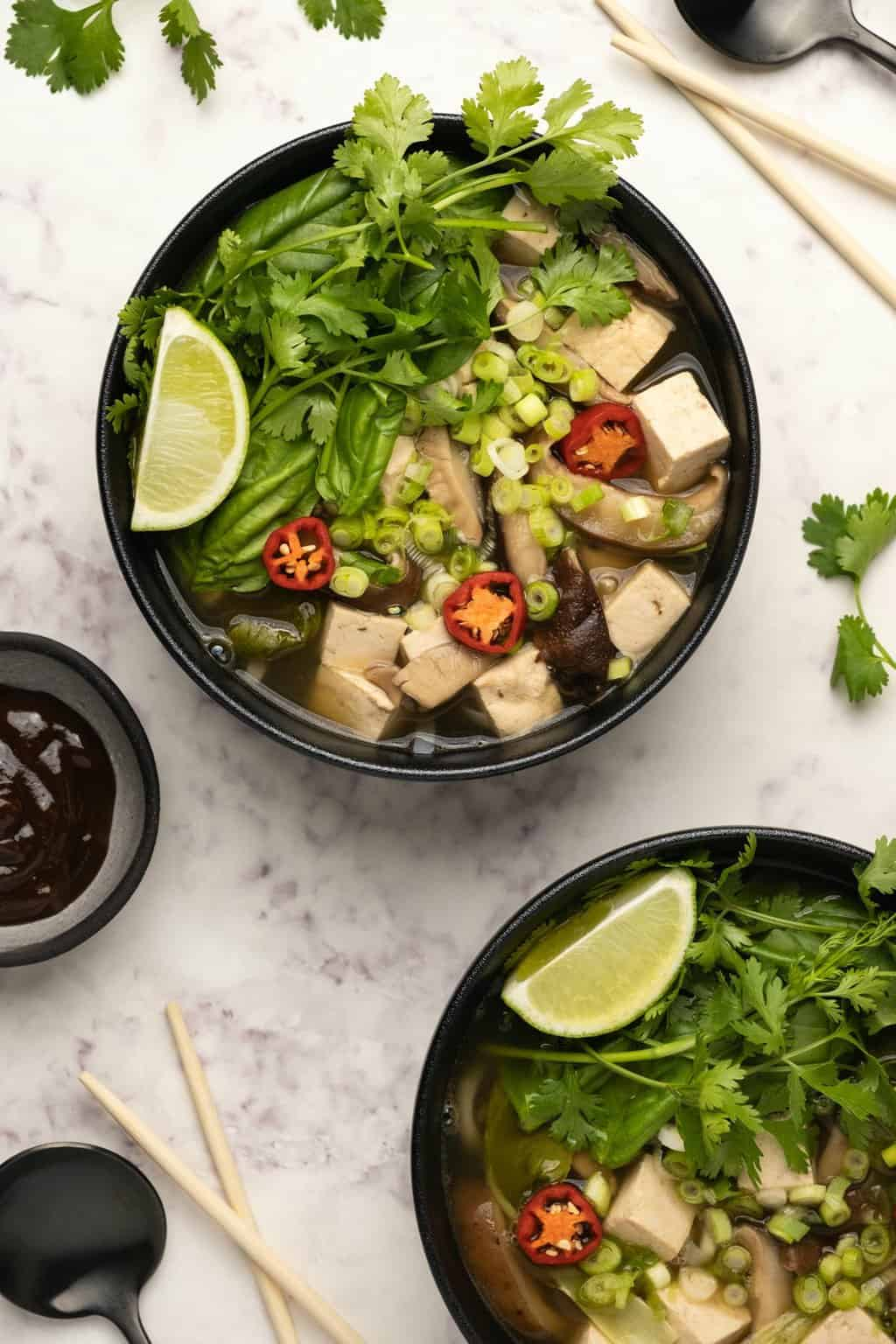 Vegan pho topped with fresh herbs and fresh lime in a black bowl.