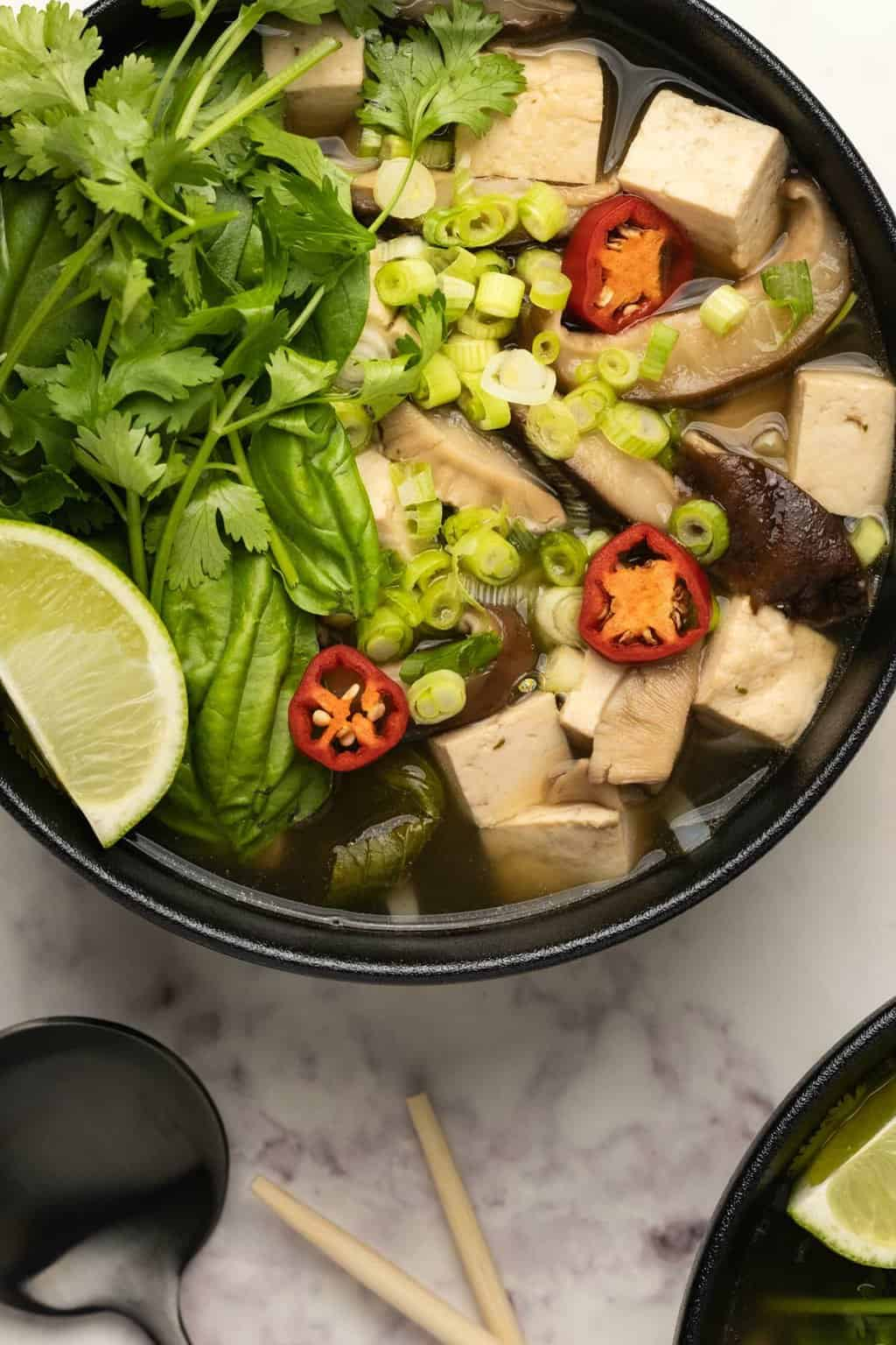 Vegan pho with fresh herbs, lime and chili in a black bowl.