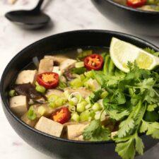 Vegan pho in black bowls.
