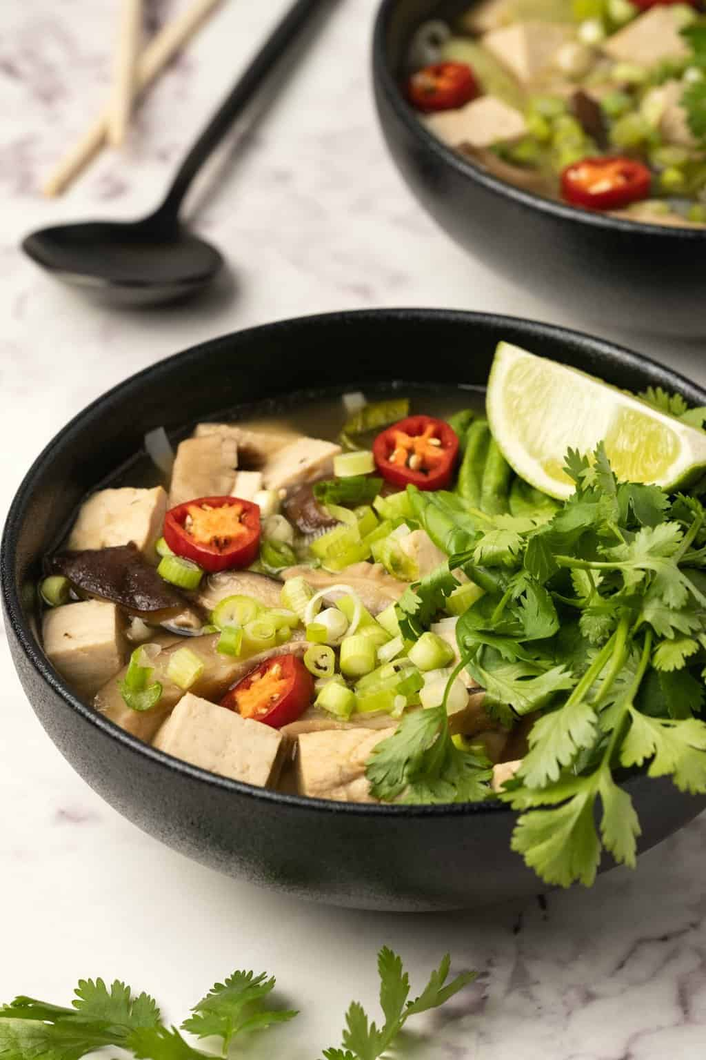 Vegan pho with fresh lime and herbs in a black bowl.