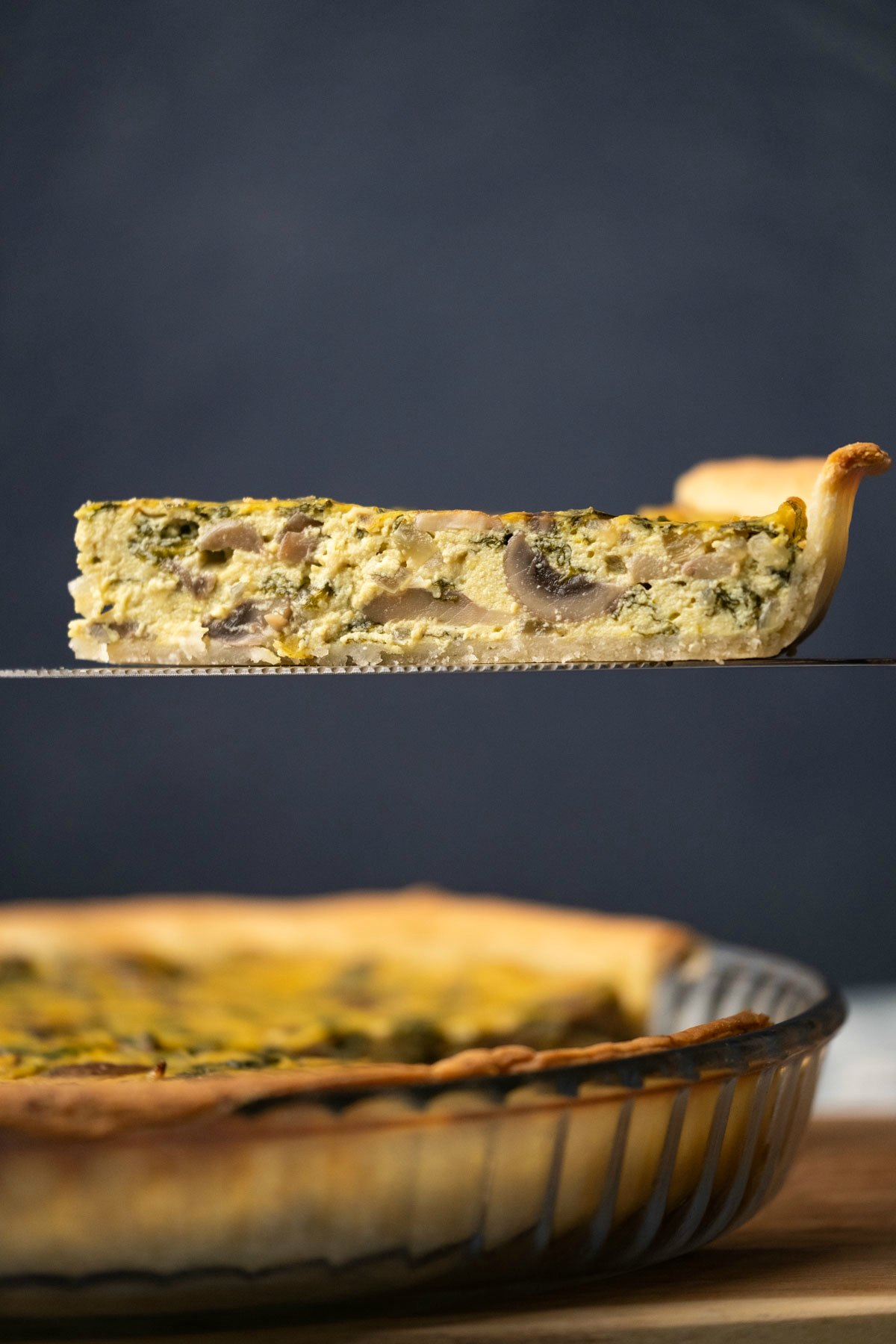 Slice of vegan quiche on a cake lifter.