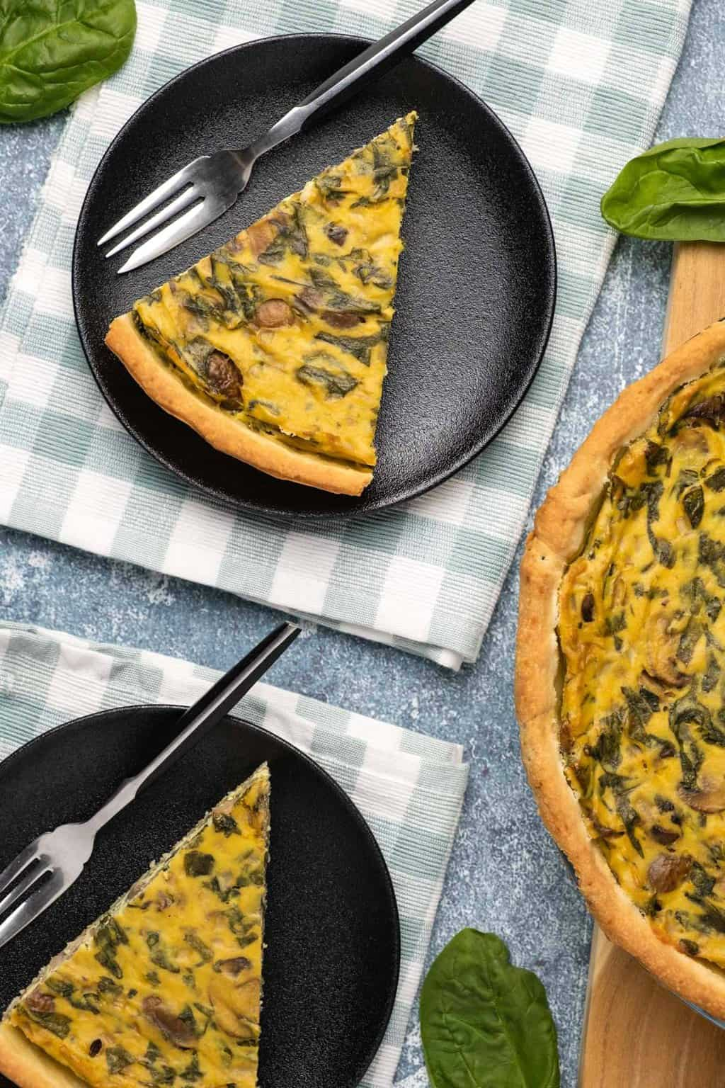 Slices of vegan quiche on black plates with forks.