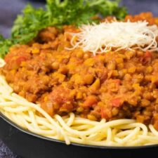 Lentil bolognese with spaghetti and vegan parmesan in a black bowl.