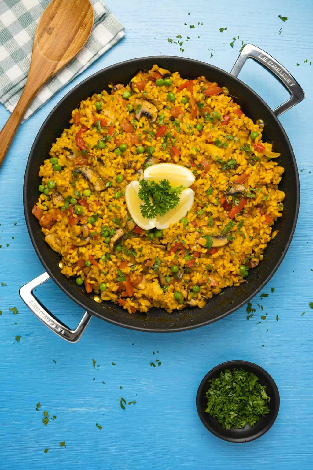 Vegan paella topped with lemon wedges and chopped parsley in a black paella pan.