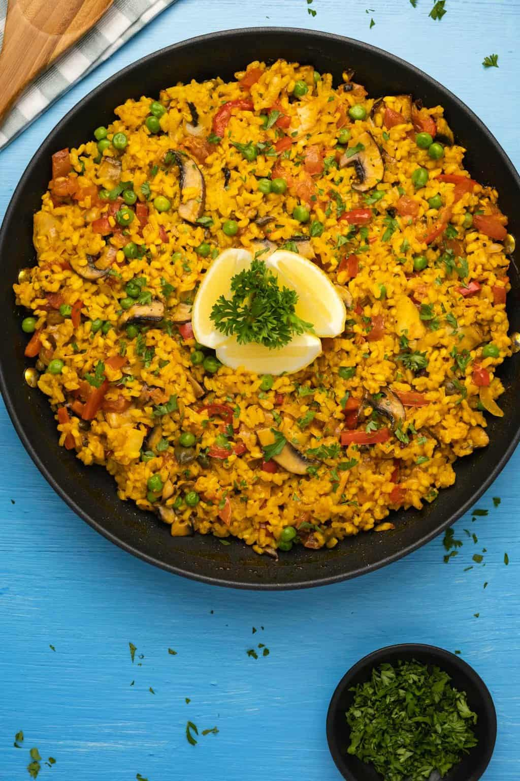 Vegetable paella in a paella pan with lemon wedges and parsley.