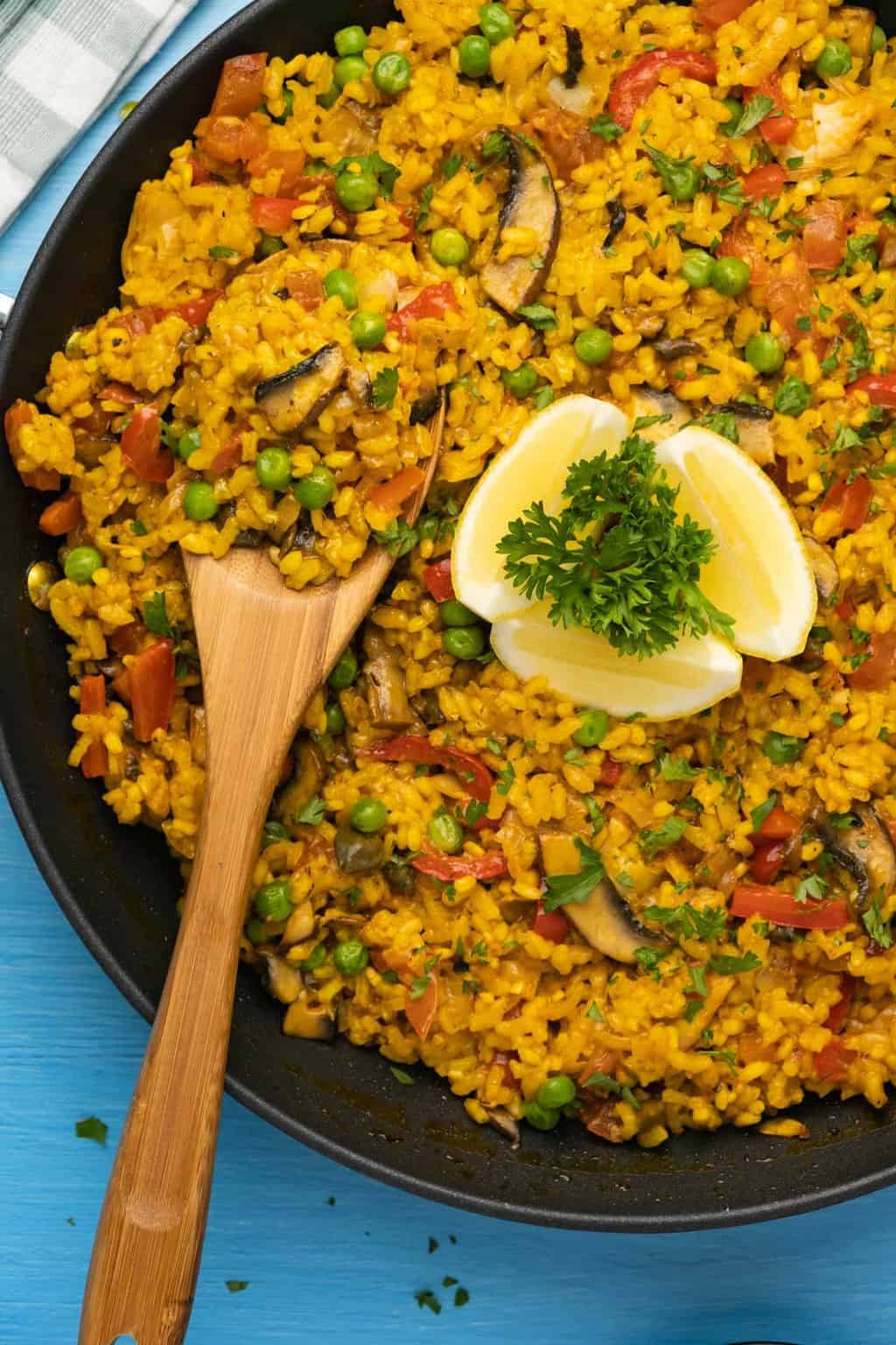 Paella in a black paella pan with a wooden spoon.