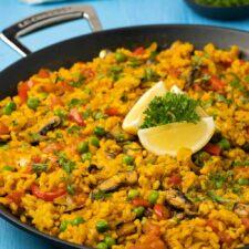 Vegan paella in a paella pan with fresh lemon and parsley.