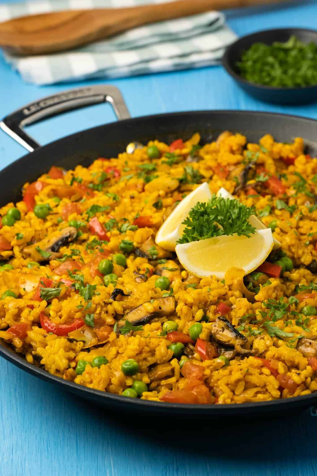 Paella topped with lemon wedges and parsley in a paella pan.