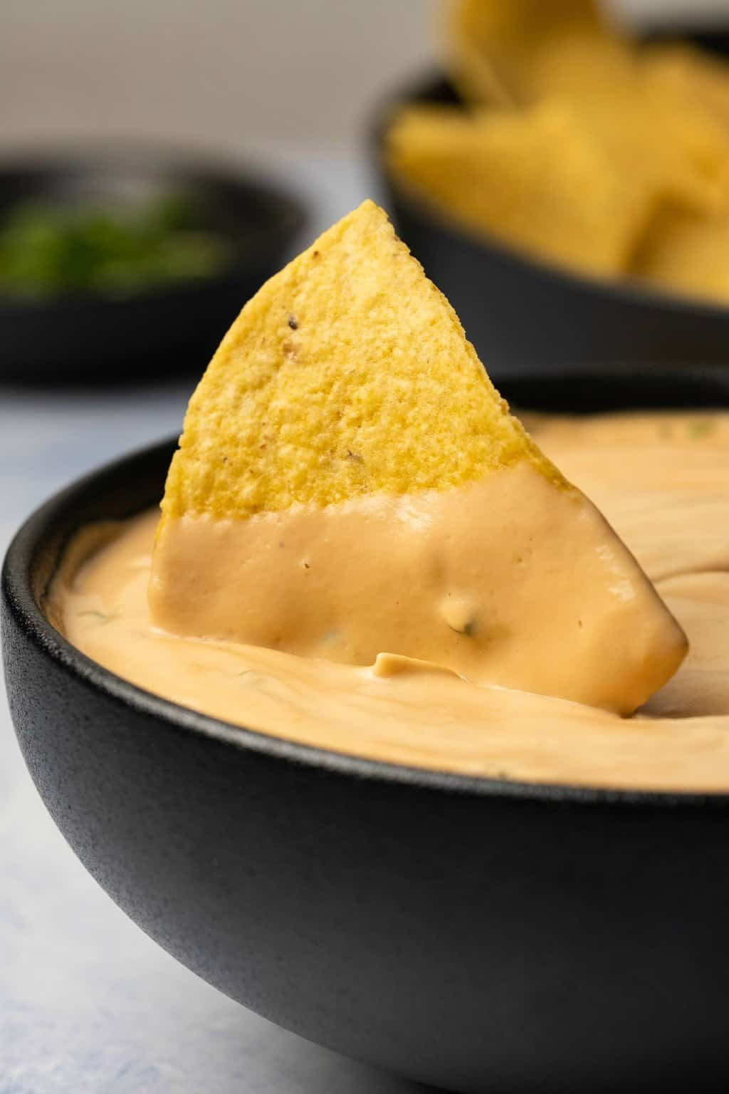 Tortilla chip in a black bowl of queso.