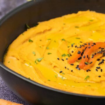 Roasted red pepper hummus in a black bowl.
