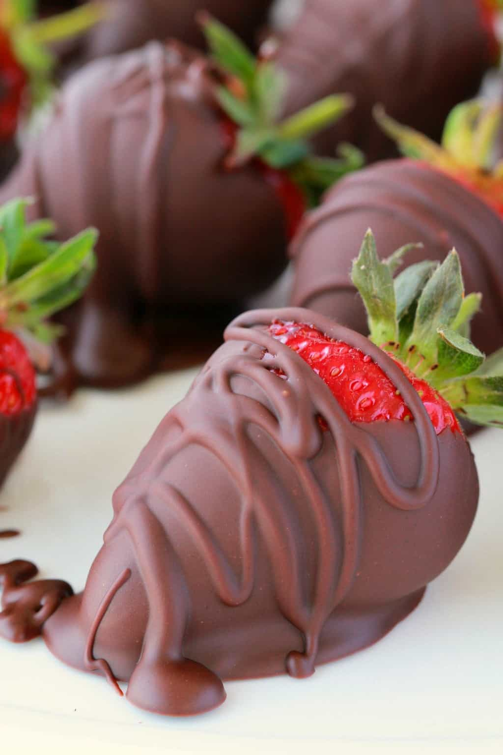Vegan chocolate covered strawberries on parchment paper.