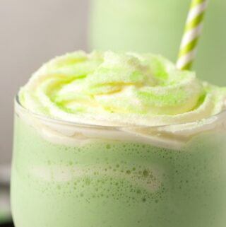 Vegan shamrock shake topped with cream and green sanding sugar in a glass with a straw.