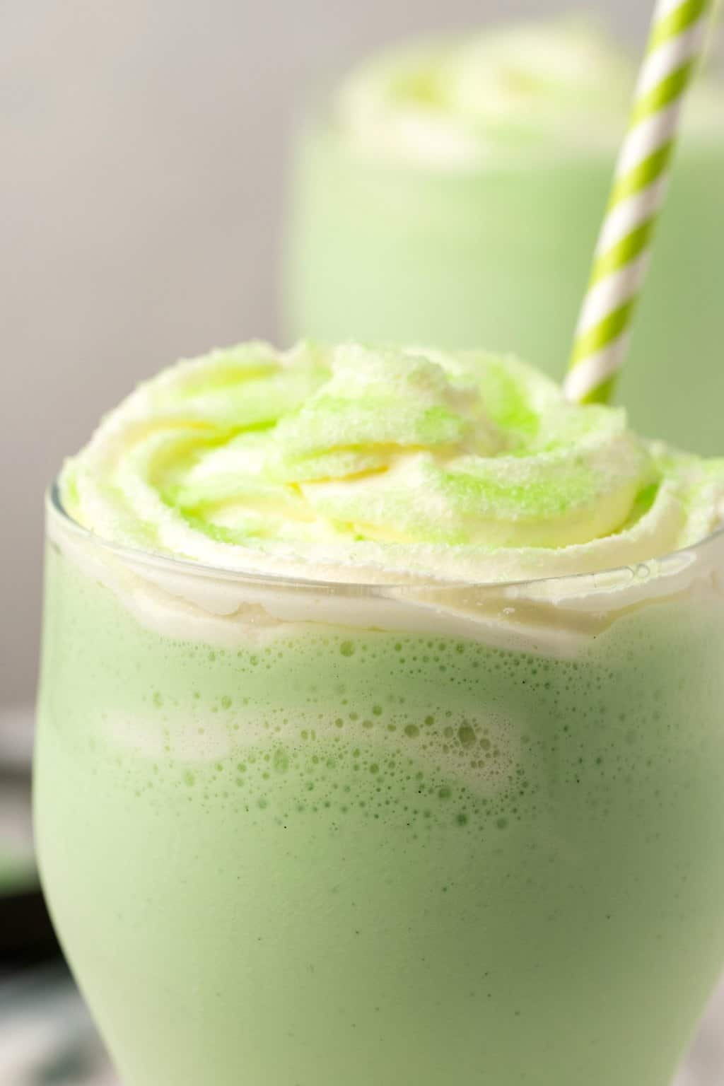 Vegan shamrock shake in a tall glass with whipped cream and green sanding sugar.