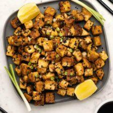 Fried tofu with lemon wedges on a black plate.