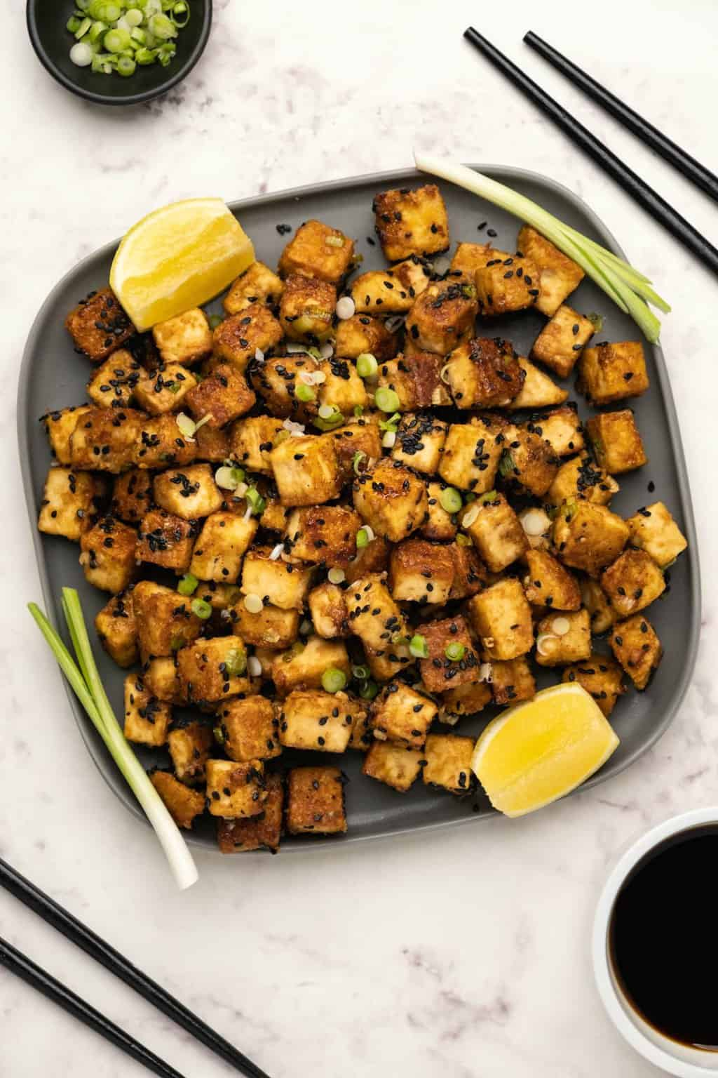 Fried Tofu with black sesame seeds and spring onion on a plate.