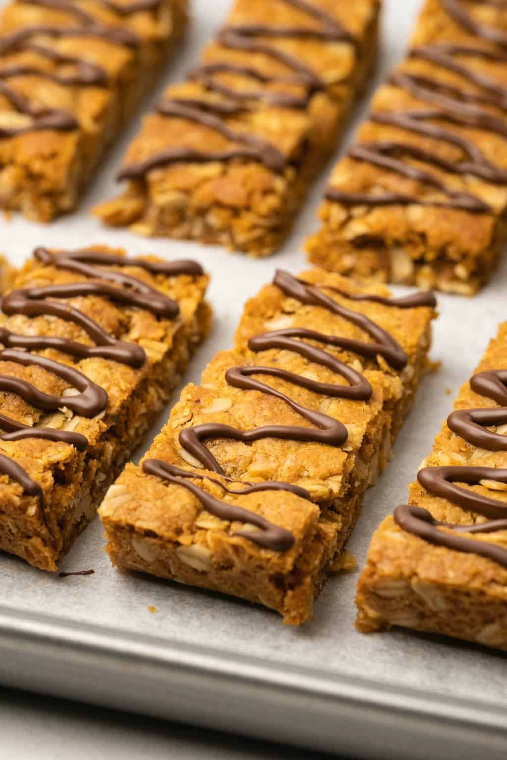 Oatmeal bars drizzled with chocolate on a parchment lined baking tray.