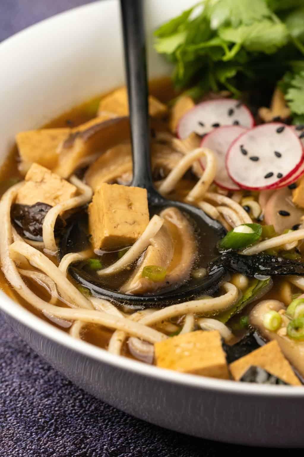 Vegan ramen in a white bowl with a black spoon.