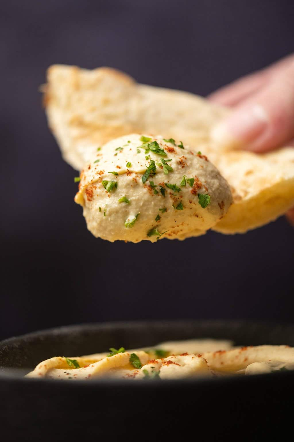A pita bread dipped into a bowl of hummus.