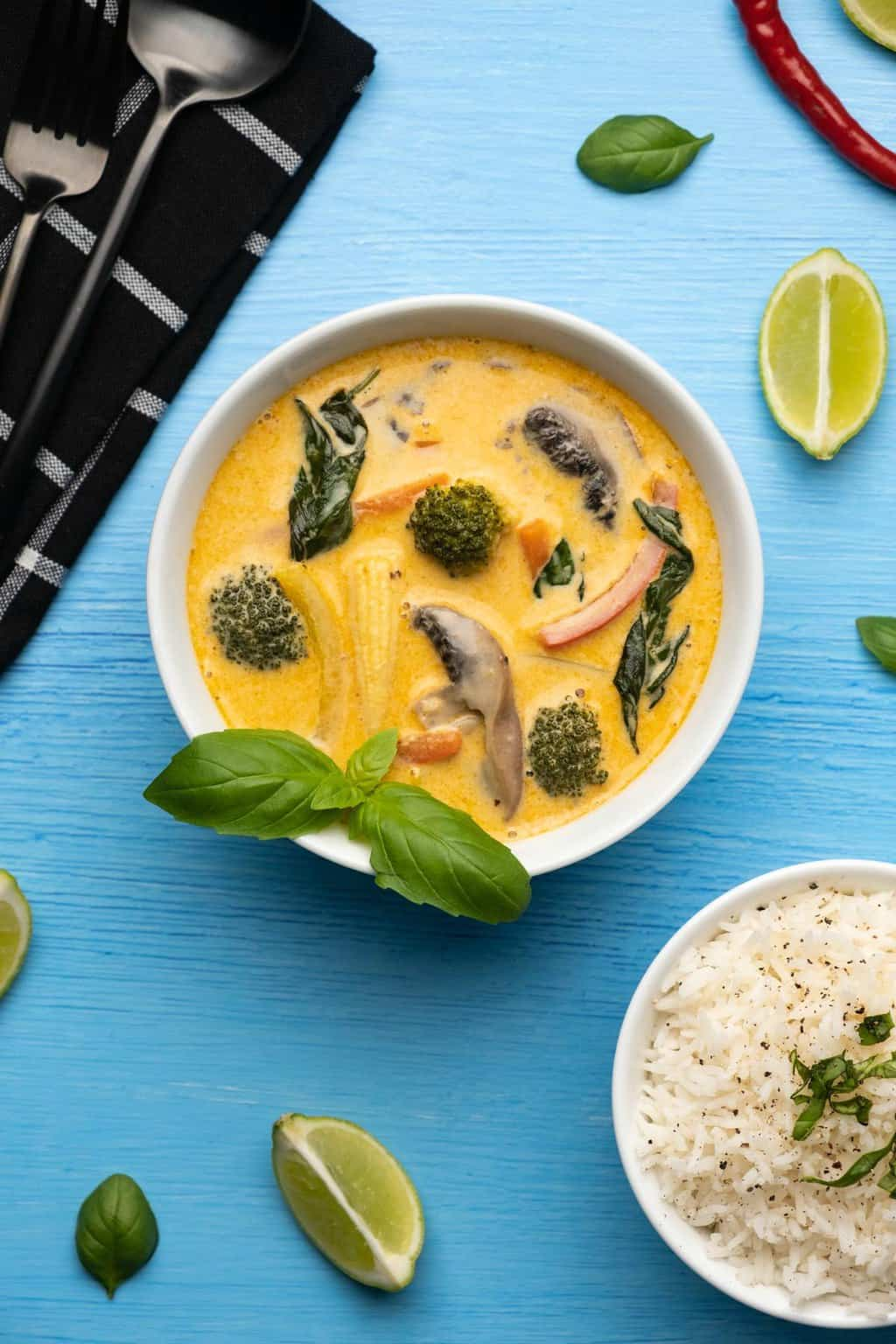 Vegan Thai red curry topped with fresh basil in a white bowl.