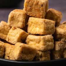 Baked tofu cubes stacked up on a black plate.