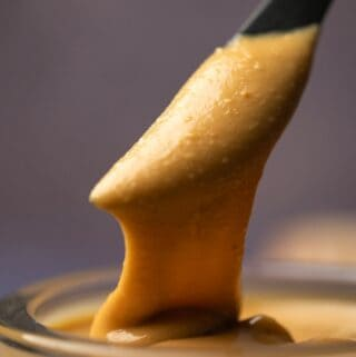 Homemade peanut butter in a glass jar with a knife.